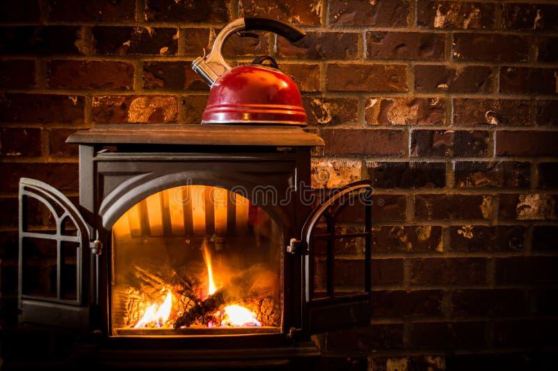 加热水壶的舒适,温暖的火反对砖壁炉边 图库摄影