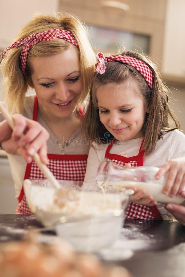 加牛奶的女儿,当母亲揉面团时 免版税库存照片