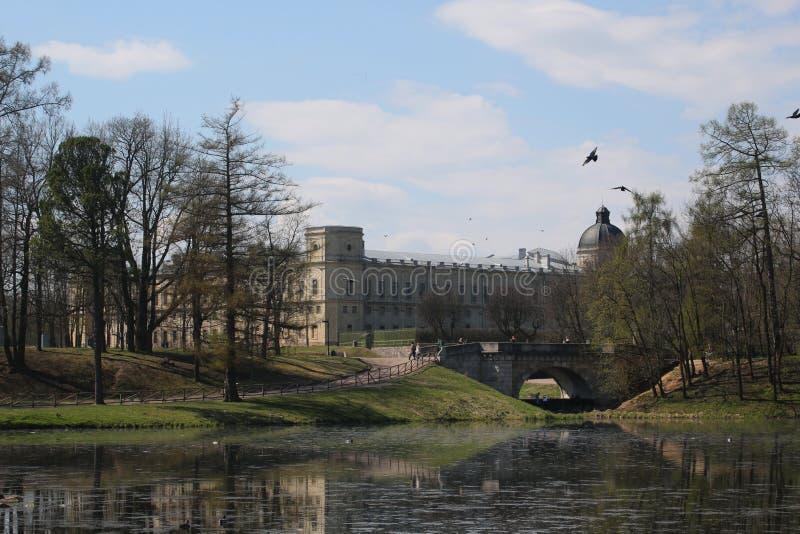 加特契纳城堡在有湖和一座石桥梁的公园 免版税图库摄影