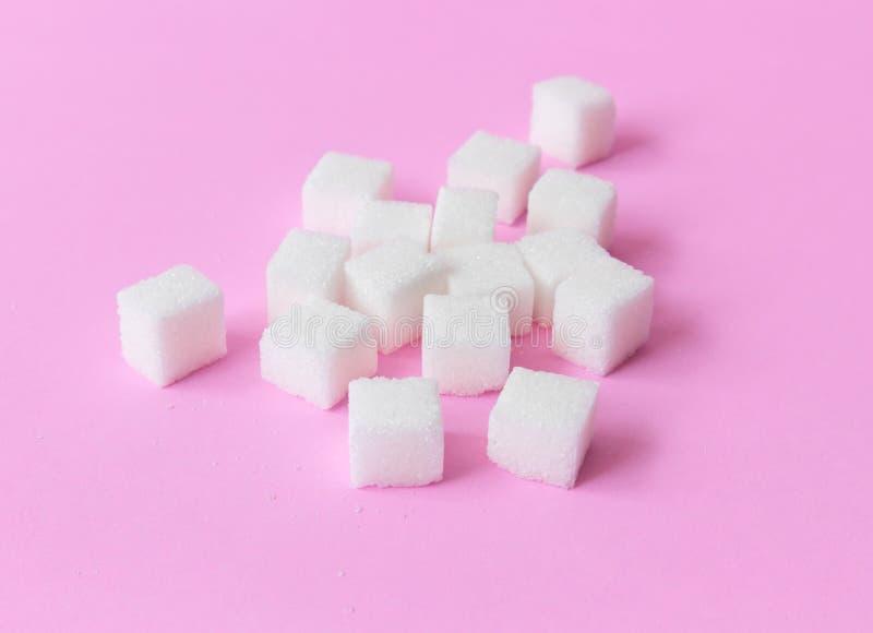 加糖在桃红色背景、食物和医疗保健概念, se的立方体 库存图片