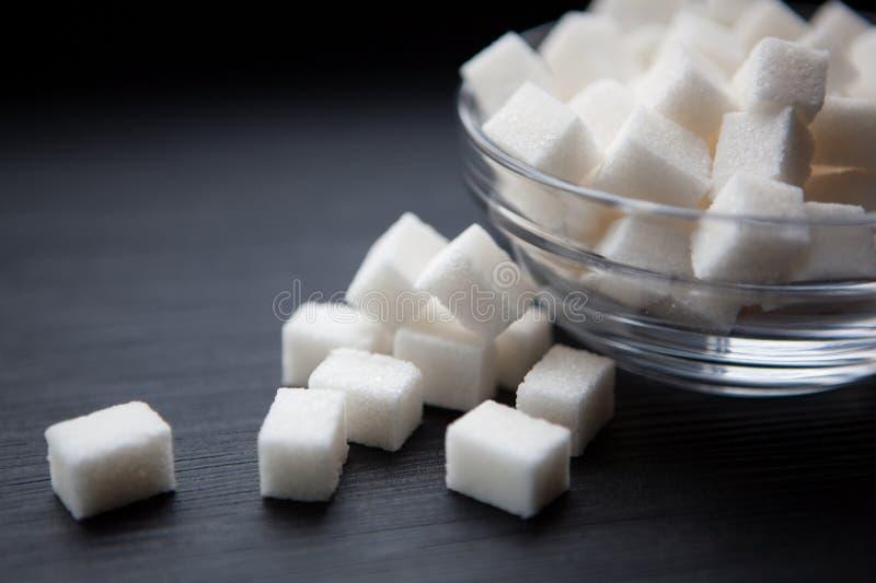 加糖在黑背景,关闭的立方体  库存照片