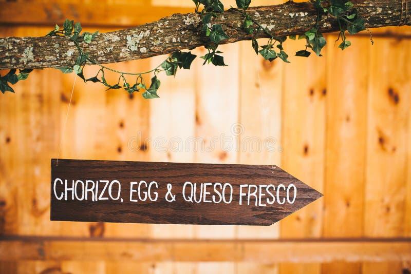 加调料的口利左香肠、蛋& queso壁画木头标志 库存图片