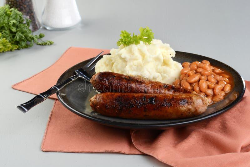 加调料的口利左香肠香肠用土豆泥和被烘烤的豆 库存照片