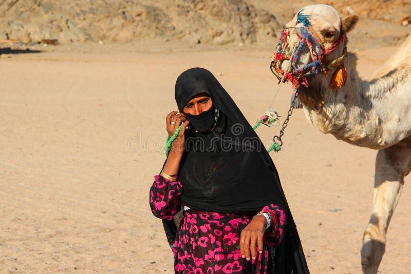 洪加达,埃及- 2015年4月24日:从流浪的村庄的老妇女cameleer在有她的骆驼的撒哈拉大沙漠,埃及, 4月的洪加达 免版税图库摄影