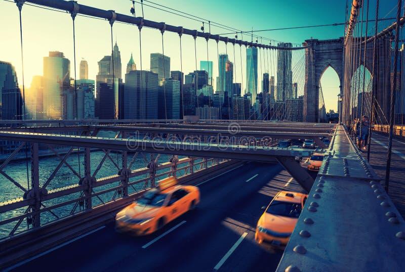 加速在布鲁克林大桥,曼哈顿的日落的Cub 其中一座最偶象的桥梁在世界上,纽约 免版税图库摄影