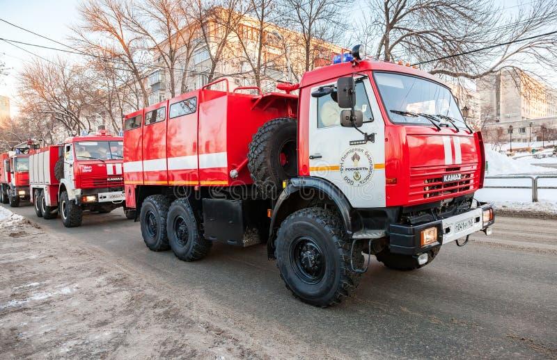 加速在街道下的红色救火车KamAZ-43114对电话 免版税库存照片