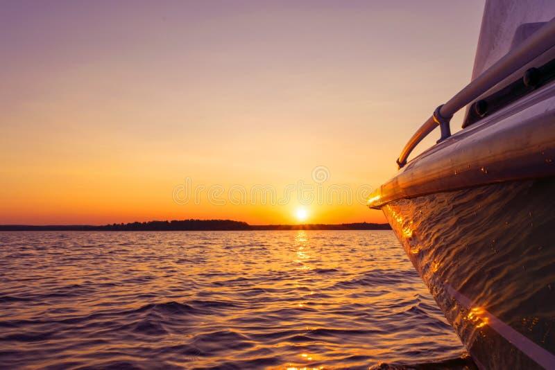 加速的侧视图钓鱼有水滴的汽船  在日落的蓝色海洋海水波浪反射 在的汽船 免版税库存图片