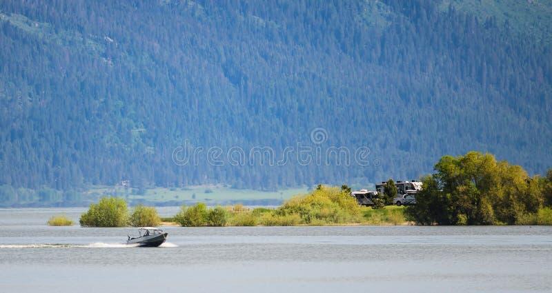 加速通过在山的湖边营地的汽艇 免版税库存照片
