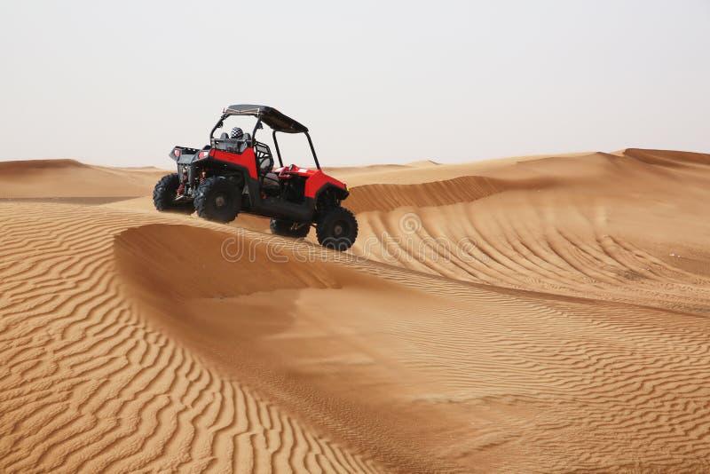 加速通过在阿拉伯人的沙丘的越野SUV车 免版税库存图片