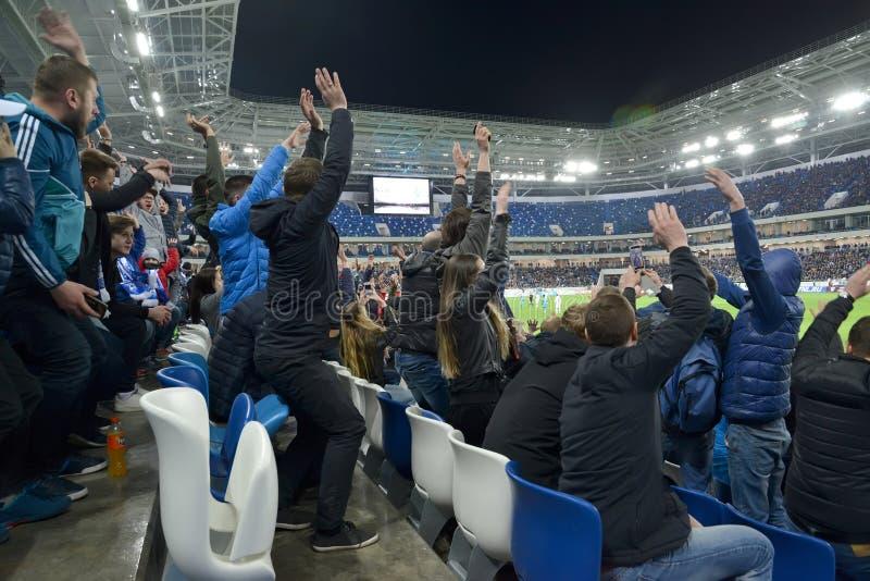加里宁格勒,俄国 一场足球比赛的观众用为喜悦被投掷的手 竞技场波罗地体育场 免版税库存图片