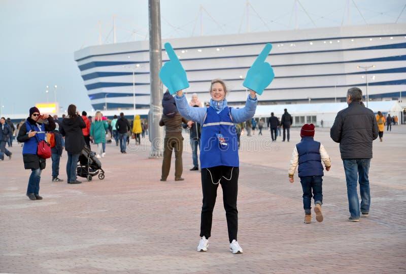 加里宁格勒,俄国 世界杯足球赛的女孩志愿者以波儿地克的竞技场体育场为背景的2018年 免版税库存图片