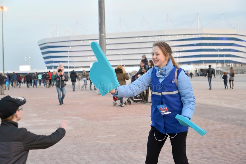 加里宁格勒,俄国 世界杯足球赛的志愿者2018年与在手上的索引 竞技场波罗地体育场 免版税图库摄影