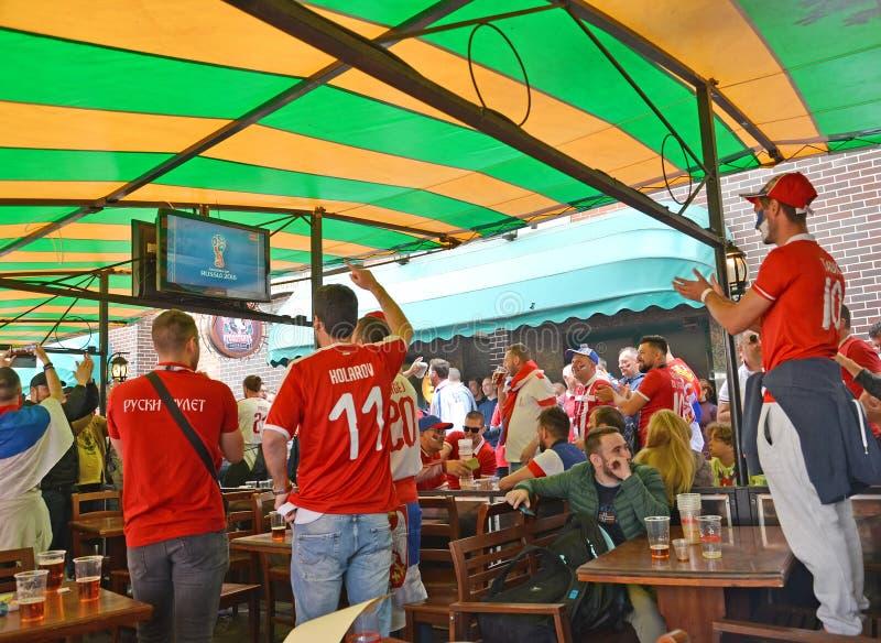 加里宁格勒,俄国 塞尔维亚爱好者喝在街道咖啡馆的啤酒和手表电视在Leninsky大道 世界杯足球赛在俄罗斯 库存照片