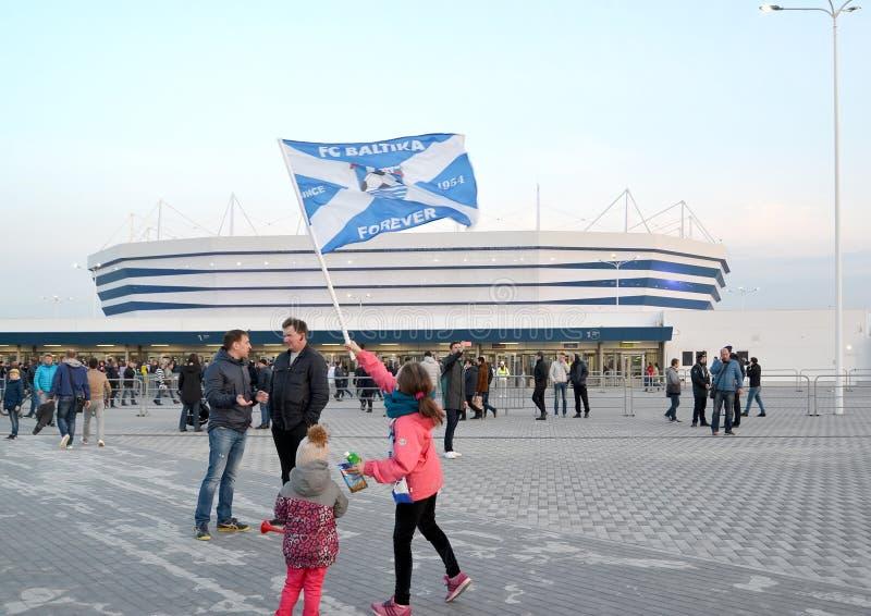 加里宁格勒,俄国 女孩挥动ffootball俱乐部Baltika旗子以波儿地克的竞技场体育场为背景 免版税图库摄影