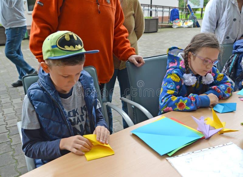 加里宁格勒,俄国 孩子学会投入origami 儿童` s大师类露天 免版税库存图片