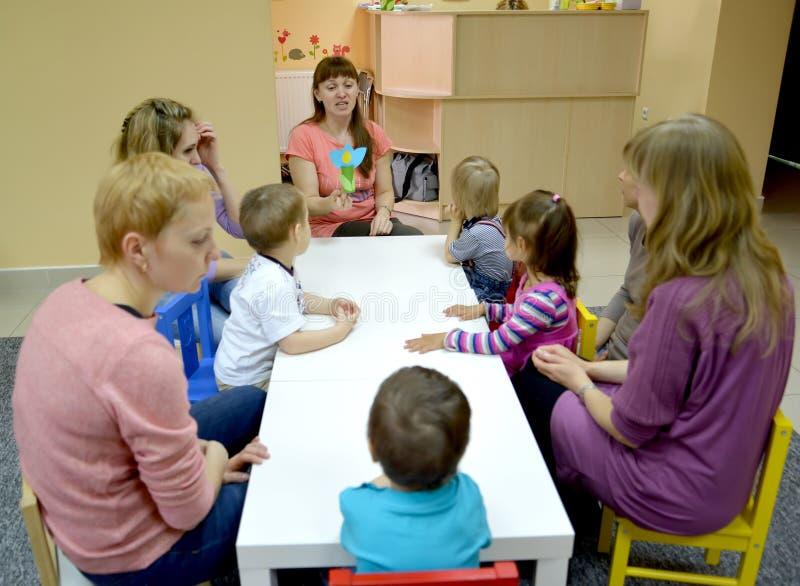加里宁格勒,俄国 家庭教师显示给有父母的孩子从纸的一个自创产品 创造性的发展演播室  图库摄影