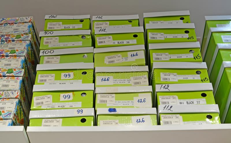 加里宁格勒,俄国 有儿童` s鞋类的箱子在堆把放在架子上在商店 免版税库存图片