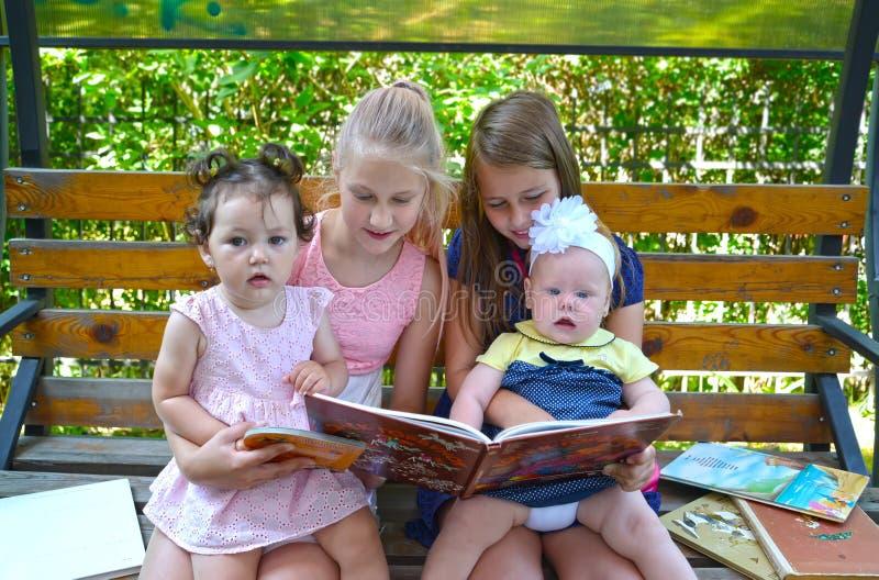 加里宁格勒,俄国 有兴趣的孩子在公园考虑在一条长凳的书 库存照片