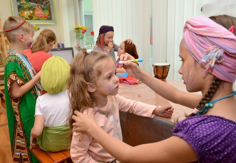加里宁格勒,俄罗斯 女孩绘一张面孔给创造性的职业的婴孩在儿童的开发的cente 免版税图库摄影