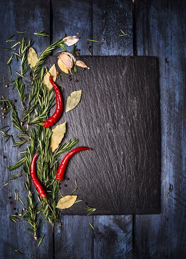 加香料与板岩的食物背景在蓝色木桌上,顶视图 免版税库存照片