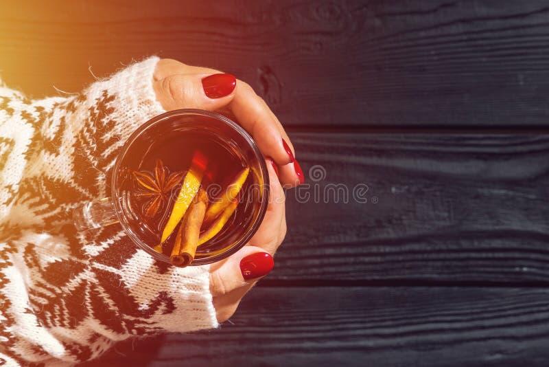 加香料的热葡萄酒在妇女的手上 免版税库存图片