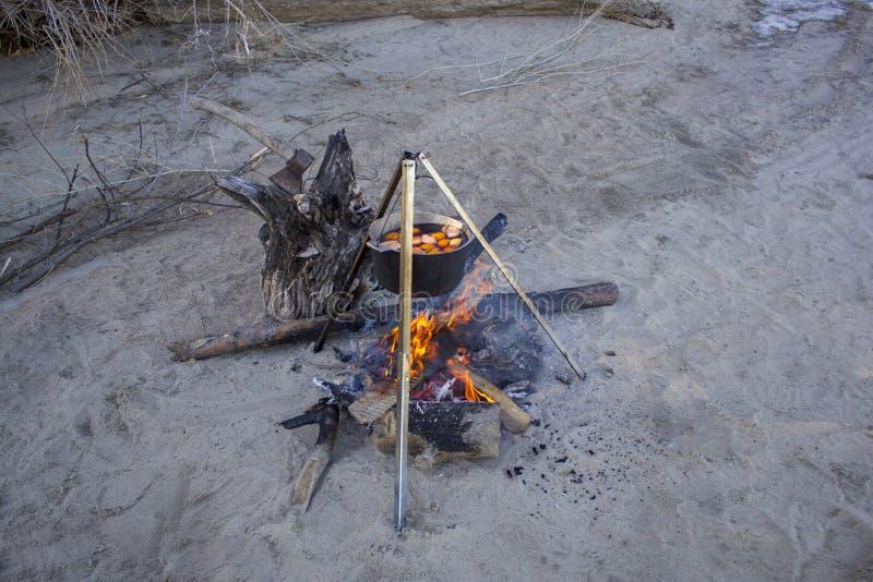 加香料的热葡萄酒用在在灰色沙子的火烹调的一口大金属大锅的果子与干燥木柴和轴 库存照片