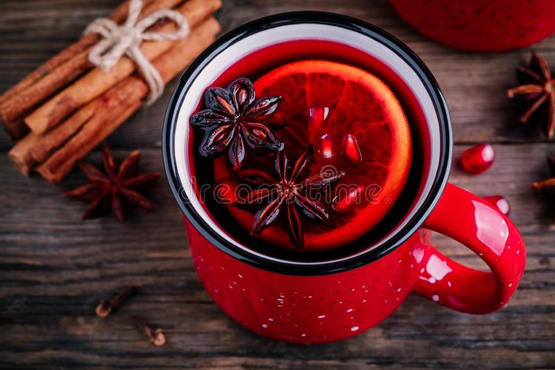 加香料的石榴苹果汁在红色杯子的加香料的热葡萄酒桑格里酒在木背景 免版税库存图片