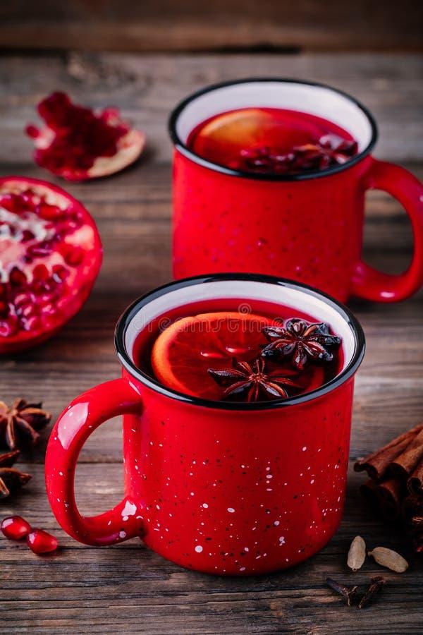 加香料的石榴苹果汁在红色杯子的加香料的热葡萄酒桑格里酒在木背景 免版税库存照片