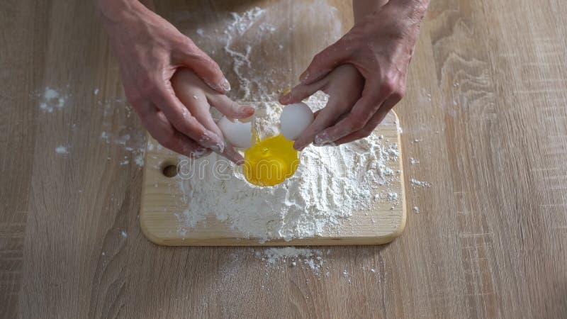 加鸡蛋的女性孩子和祖母手到面粉,家庭食谱,传统 图库摄影