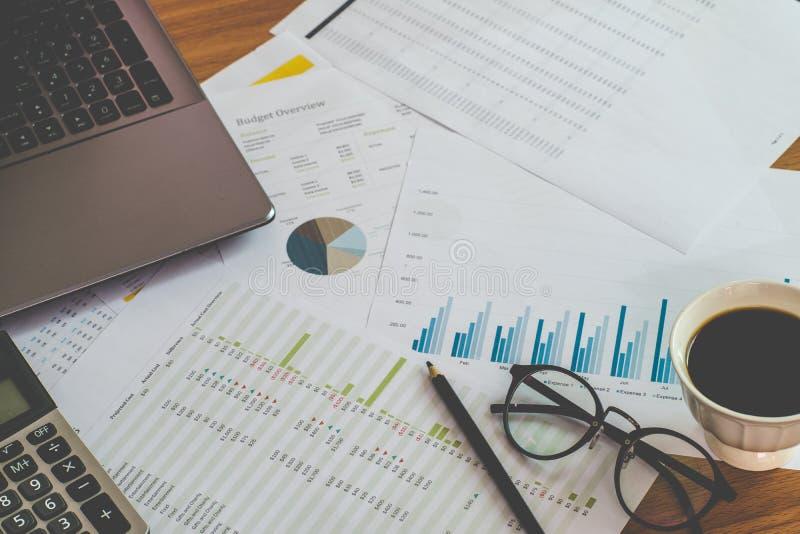 财务管理概念、计算器和私人预算的许多文件与一台膝上型计算机的在桌上 免版税库存照片
