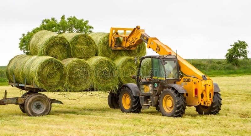 移动一个圆的大包的装载者拖拉机从领域 免版税库存照片