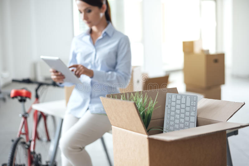移动一个新的办公室的女商人 免版税库存照片