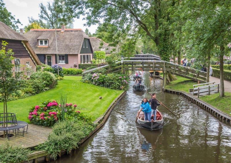 移动一条传统船夫小船的游人通过运河  免版税库存照片
