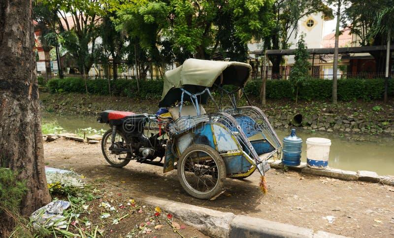 动力化的三轮车在三宝垄拍的一张肮脏的河照片旁边停放印度尼西亚 免版税库存图片