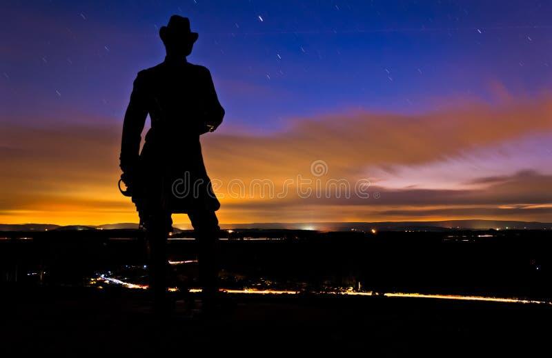 移动在晚上被采取的长的曝光的一个雕象后的云彩和星从一点桅顶下桅盘在葛底斯堡,宾夕法尼亚 库存图片