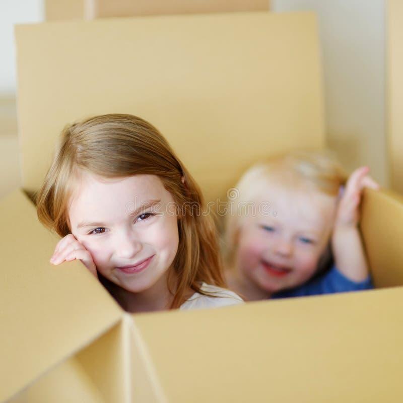 移动她新的家的两个逗人喜爱的姐妹 库存照片