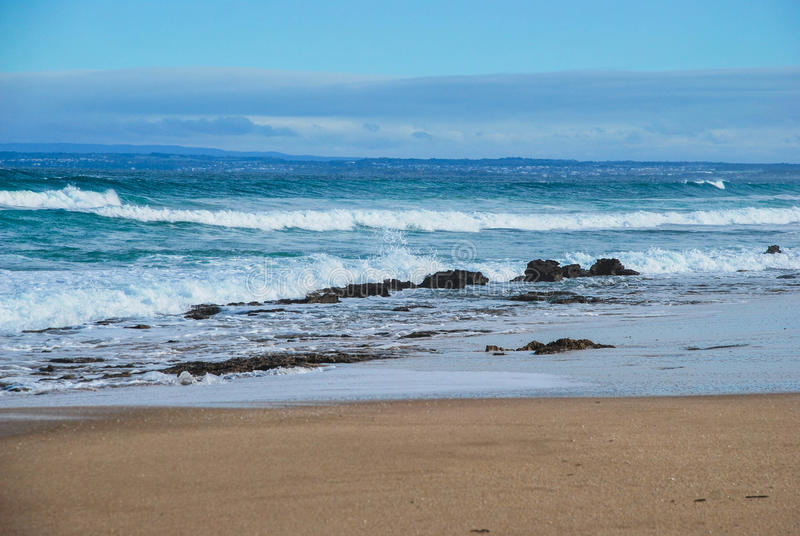 滚动对沙滩,背景的居民土地的海浪 海洋树丛,维多利亚,澳大利亚 免版税库存照片