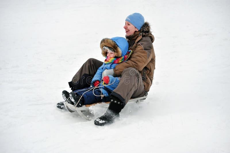 滚动爬犁的母亲和孩子家庭  免版税库存图片