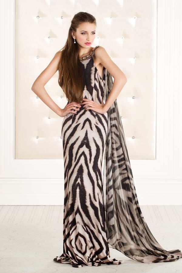 动物印刷品长的礼服的美丽的妇女 免版税库存照片