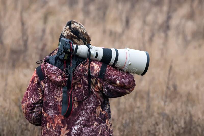 动物摄影师 照片猎人 伪装制服的一个人有一台黑照相机和一个大白色透镜的 有照相机的一个人 免版税库存照片