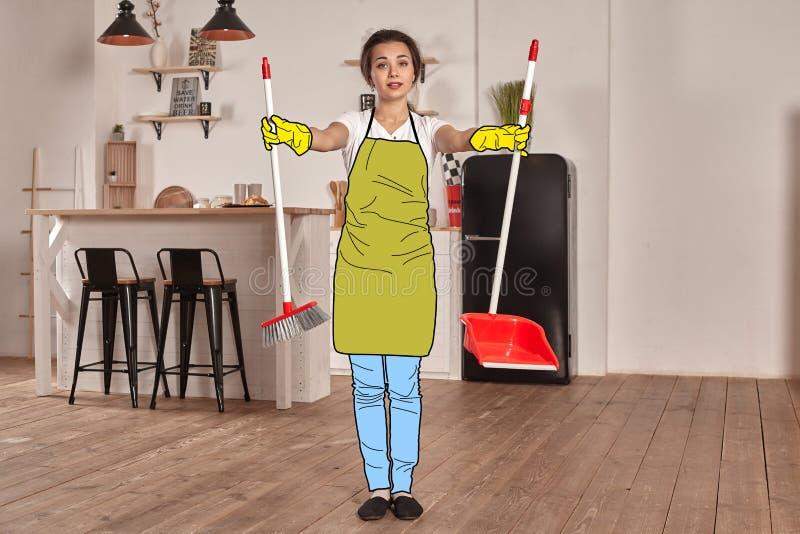 动画片牛仔裤、围裙和橡胶手套的美女摆在反对与刷子的厨房背景和  免版税图库摄影