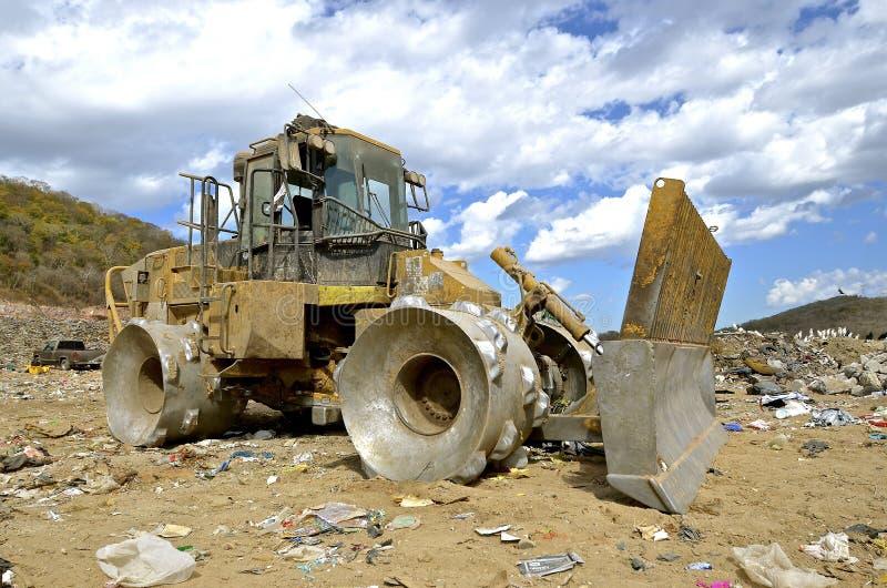 移动的垃圾的巨大的拖拉机在转储 免版税库存图片