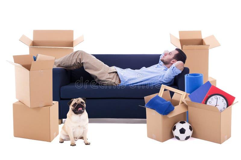 移动的天概念-供以人员说谎在有棕色纸板boxe的沙发 免版税库存图片