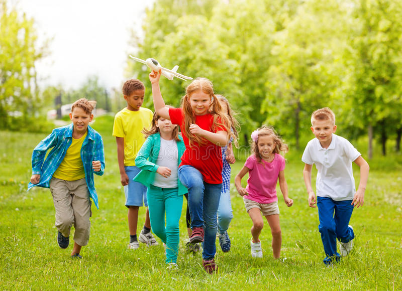 移动的女孩拿着飞机玩具和孩子后边 库存图片
