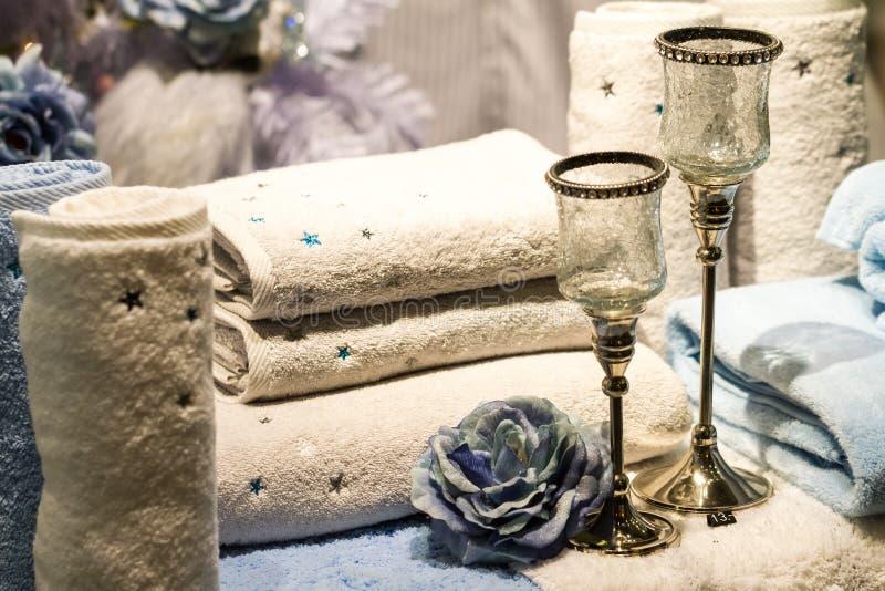 滚动的毛巾、蓝色玫瑰和蜡烛台 免版税库存图片