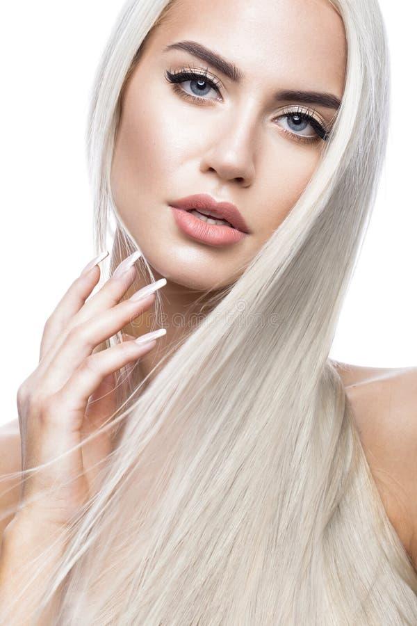 移动的美丽的白肤金发的女孩与一根完全光滑的头发和经典构成 秀丽表面 免版税库存照片