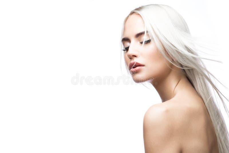 移动的美丽的白肤金发的女孩与一根完全光滑的头发和经典构成 秀丽表面 库存图片
