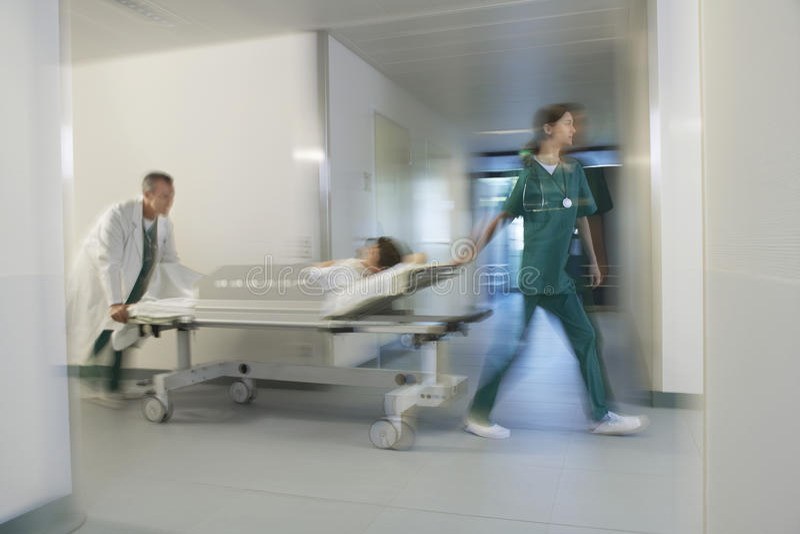 移动盖尼式床的医师患者通过医院走廊 免版税图库摄影