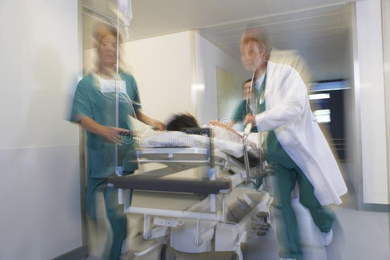 移动盖尼式床的医师患者通过医院走廊 免版税库存图片