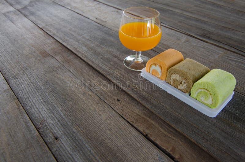 滚动蛋糕用橙汁在木背景 免版税图库摄影